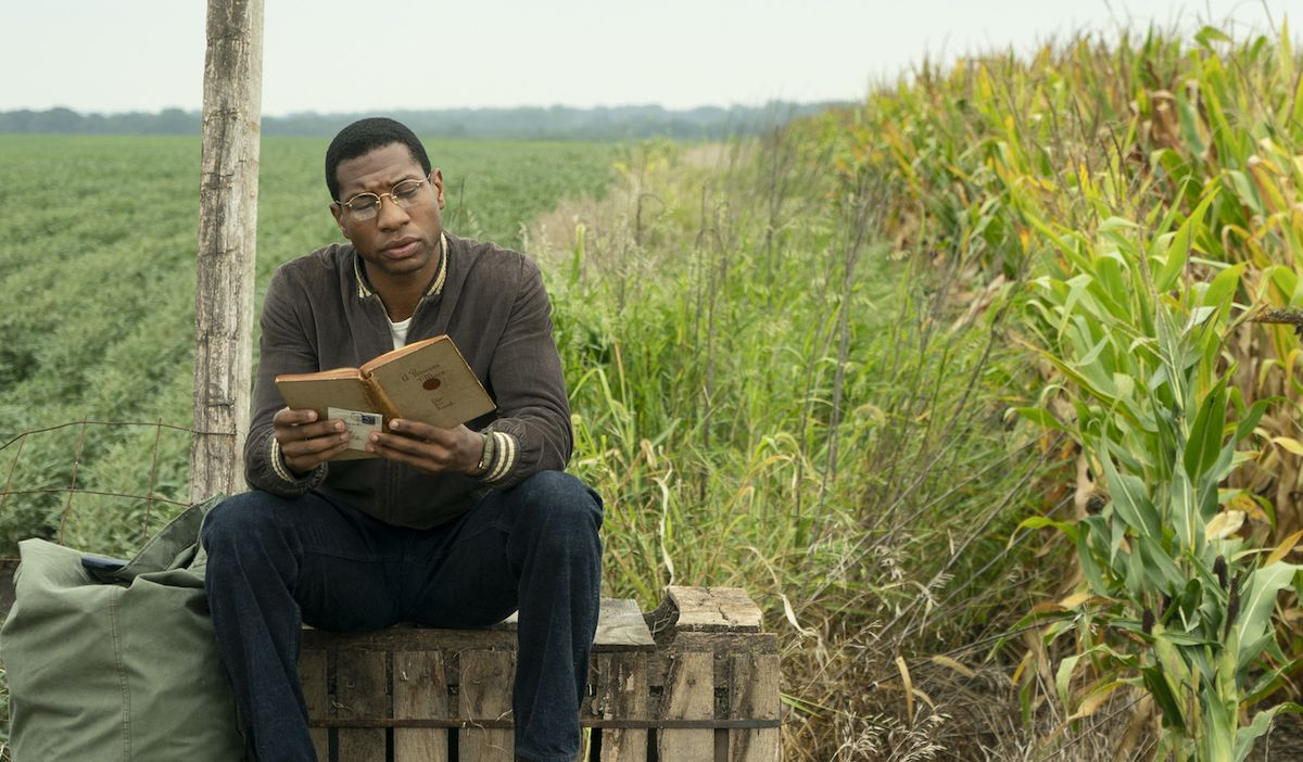 Lovecraft Country (2020). Alone in a green field is Tick Freeman, sitting on a crate reading a book besides a green sack. He is wearing round glasses and a brown jacket over a white t-shirt and dark blue jeans. He looks concentrated on what he is reading.