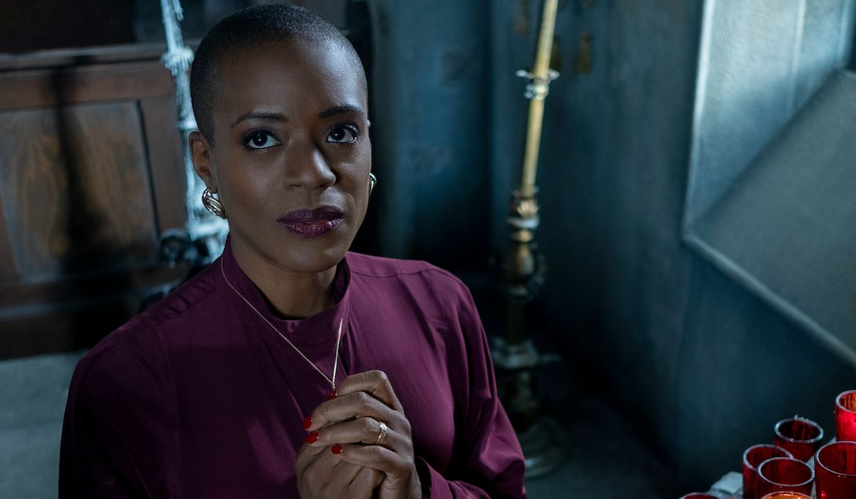 T'Nia Miller as Hannah in The Haunting of Bly Manor. Hannah is standing in a small chapel, in front of an arrangement of memorial candles. She gazes up to the ceiling, clasping her cross necklace.